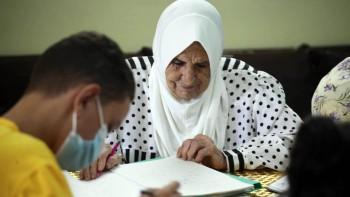 امرأة في عمر الثمانين تعلم الأطفال الرياضيات